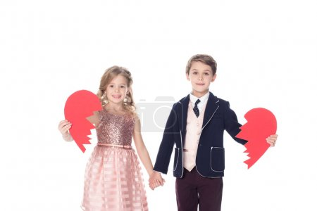 cute little kids holding pieces of broken heart symbol and smiling at camera isolated on white