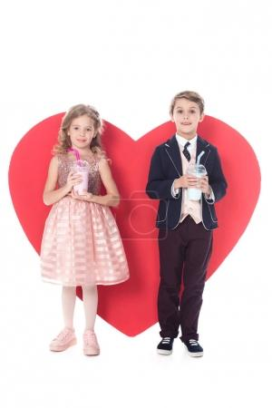 adorable little children holding milkshakes in plastic cups and big red heart symbol behind isolated on white