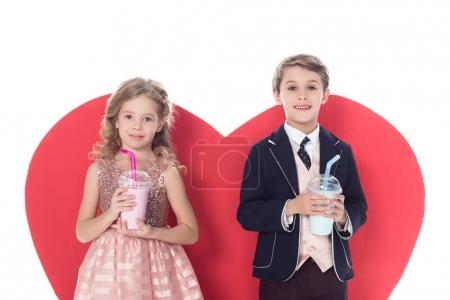 cute little kids holding milkshakes in plastic cups and big red heart symbol behind isolated on white