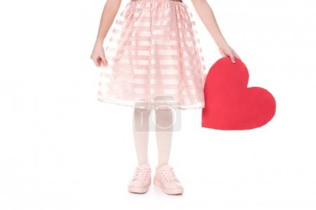 cropped shot of little child in pink dress holding red heart symbol isolated on white