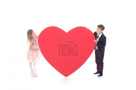 adorable little kids holding big red heart symbol isolated on white