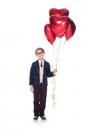 cute little boy in suit and eyeglasses holding red heart shaped balloons and smiling at camera isolated on white
