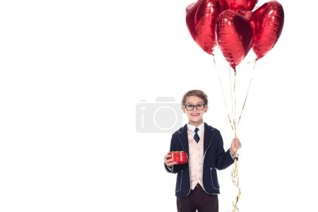cute little boy in suit and eyeglasses holding red heart shaped balloons and gift box isolated on white