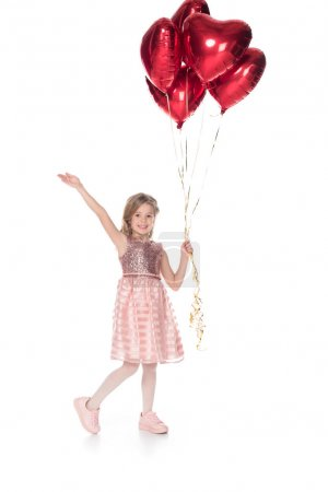 beautiful child in pink dress holding heart shaped balloons and smiling at camera isolated on white