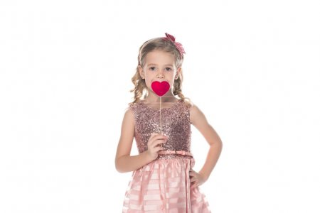 adorable little kid in pink dress holding red heart on stick and looking at camera isolated on white