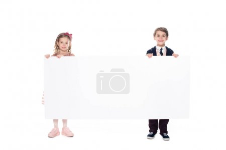 cute little kids holding blank banner and smiling at camera isolated on white
