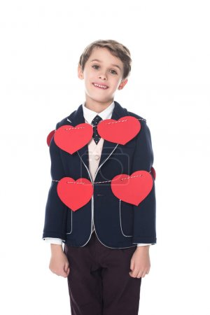 cute little boy in suit staying tied with rope and red hearts, smiling at camera isolated on white