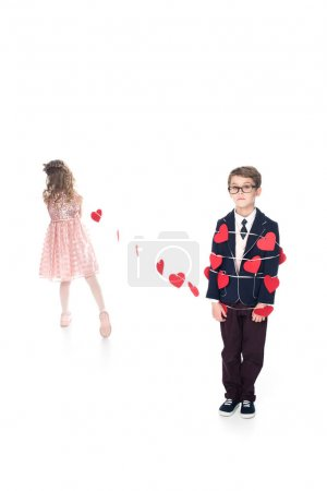 cute little girl tying boy in eyeglasses with rope and red hearts isolated on white