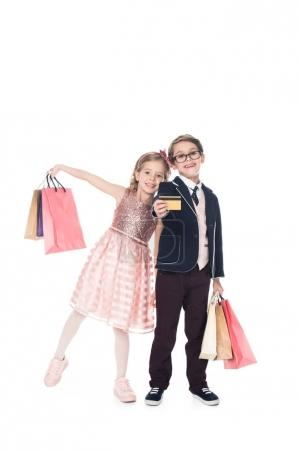cute fashionable children with paper bags and credit card smiling at camera isolated on  white