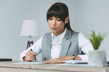 businesswoman signing contract at table isolated on gray