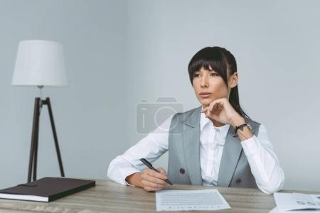 thoughtful businesswoman signing contract isolated on gray