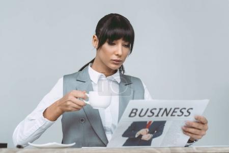 femme d'affaires lire journaux et boire du café isolé sur gris