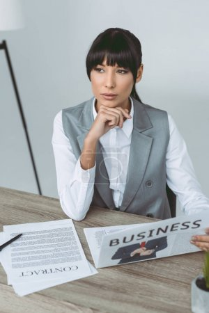 thoughtful businesswoman resting chin on hand isolated on gray