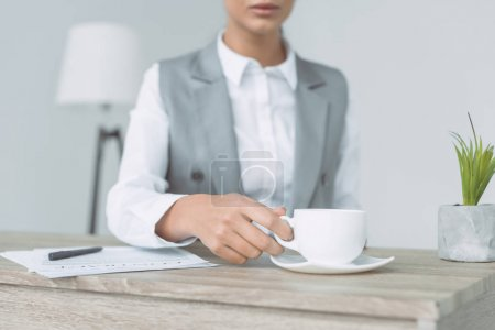 cropped image of businesswoman taking cup isolated on gray