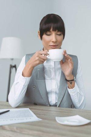 femme d'affaires attrayant, boire du café avec des yeux fermés isolés sur gris