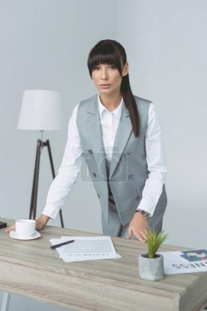 attractive businesswoman standing at table isolated on gray