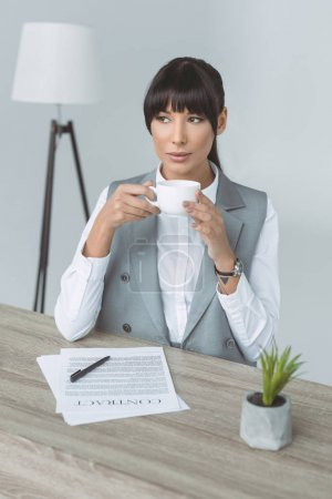 attractive businesswoman drinking coffee and looking away isolated on gray