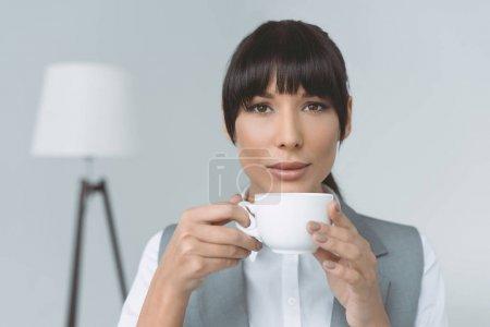 Photo pour Femme d'affaires attrayant boire du café et de regarder la caméra isolée sur gris - image libre de droit
