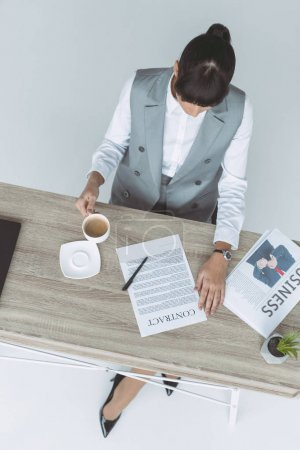 overhead view of businesswoman drinking coffee and reading contract isolated on gray