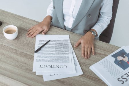 cropped image of businesswoman sitting at table with contract and documents