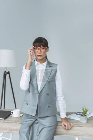 businesswoman touching glasses and looking at camera isolated on gray