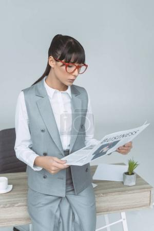 businesswoman leaning on table and reading newspaper isolated on gray