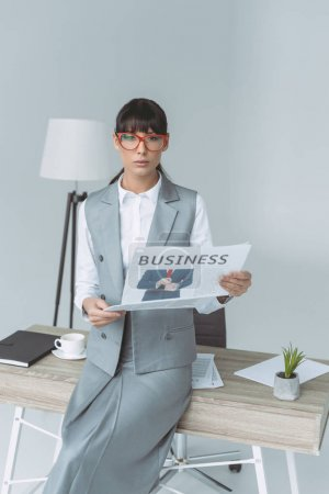 Photo for Businesswoman holding newspaper and looking at camera isolated on gray - Royalty Free Image