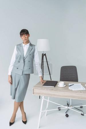 Photo pour Femme d'affaires debout à table et regardant la caméra isolée sur gris - image libre de droit