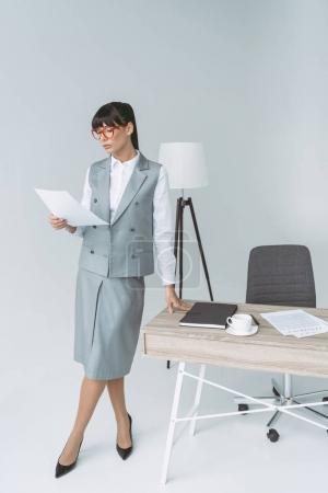 Photo pour Femme debout au tableau et en regardant les documents sur gris - image libre de droit