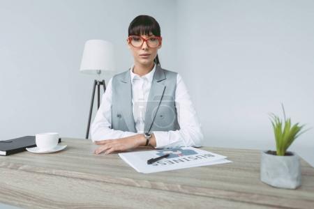 Photo pour Femme d'affaires assise à la table de travail et regardant la caméra isolée sur gris - image libre de droit
