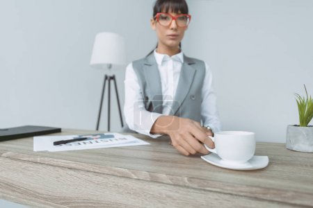 Photo for Businesswoman taking cup of coffee at table isolated on gray - Royalty Free Image