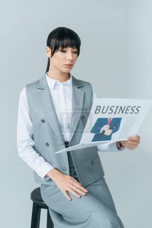businesswoman sitting on chair and reading business newspaper isolated on gray