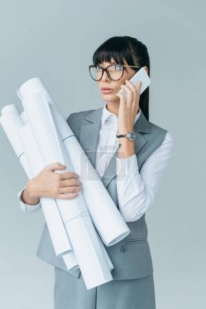 businesswoman holding blueprints and talking by smartphone isolated on gray
