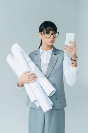 businesswoman holding blueprints and taking selfie with smartphone isolated on gray