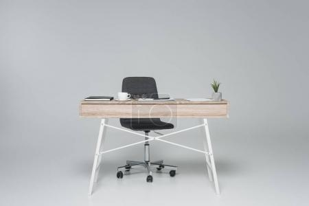 Office table with empty chair on gray...