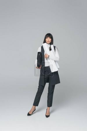 businesswoman standing with briefcase and blueprints on gray