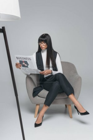 beautiful brunette businesswoman reading newspaper in armchair on gray
