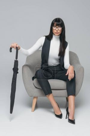 attractive brunette businesswoman sitting on armchair with umbrella on gray