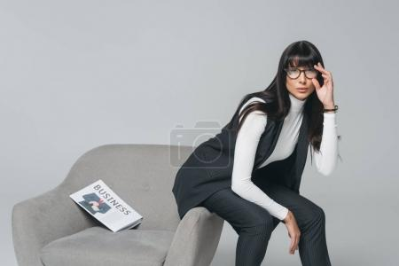 attractive brunette businesswoman sitting on armchair isolated on gray