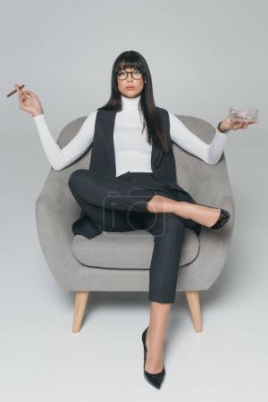 businesswoman holding ashtray and cigar and sitting in armchair on gray