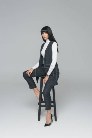 attractive brunette woman sitting on black chair on gray
