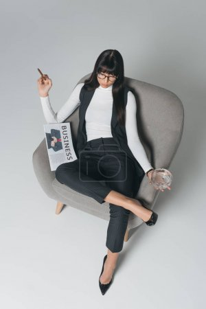 overhead view of businesswoman smoking in armchair on gray