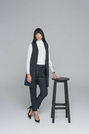 attractive brunette woman standing near wooden chair on gray