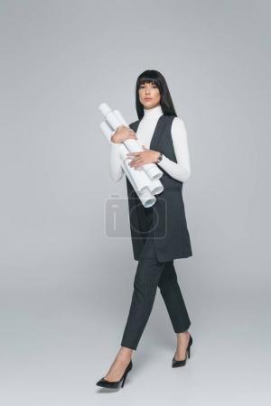female architect walking with blueprints on gray