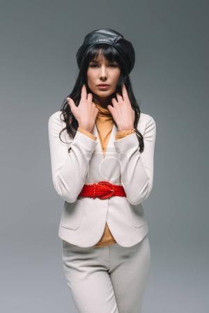 belle femme brune en costume blanc isolé sur gris