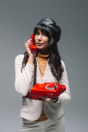 attractive brunette woman in white suit talking by red landline phone isolated on gray
