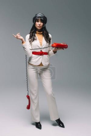attractive brunette woman in white suit with red landline phone on gray