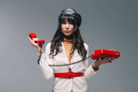 attractive brunette woman in white suit with red landline phone isolated on gray