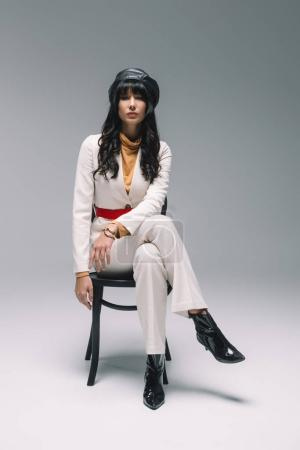 attractive brunette woman in white suit sitting on chair on gray