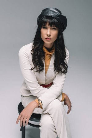beautiful brunette woman in white suit sitting on chair and looking at camera isolated on gray